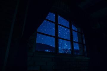 Night scene of stars seen through the window from dark room. Night sky inside dark room.