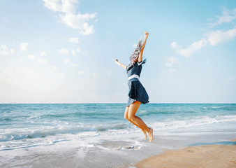 Happy woman jumping on beach on vacations.