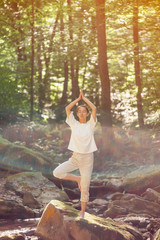 Woman practicing yoga in pose of tree in forest.