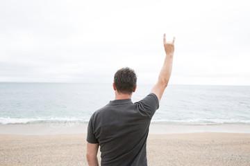 Fototapeta Male raising his arm with Devil Horns