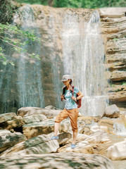 Explorer woman walking in front of waterfall.