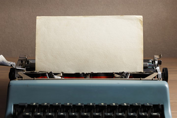 Vintage typewriter with aged textured paper sheet. Space for your text.