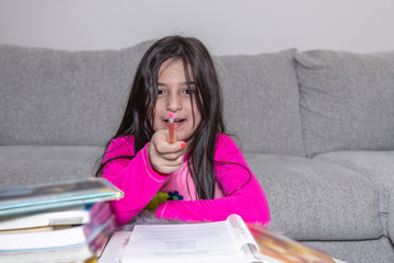A young girl doing her homework is pointing the pencil