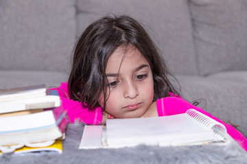 A young girl is attentively reading a book