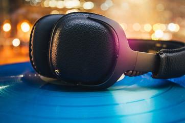 Kopfhörer auf einer blauen Schallplatte mit hellen Lichtern im Hintergrund bei Nacht