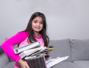 A standing young girl is carying a pile of books