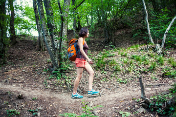The girl with a backpack is walking through the forest.