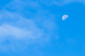 Partial moon against a blue morning sky