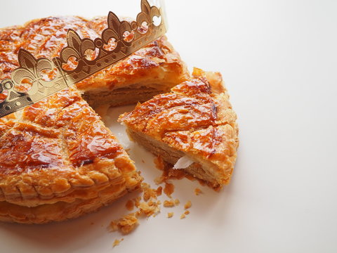 Homemade Epiphany cake or Twelfth Night cake (french galette des rois) made of puff pastry and frangipane (almond cream), white background