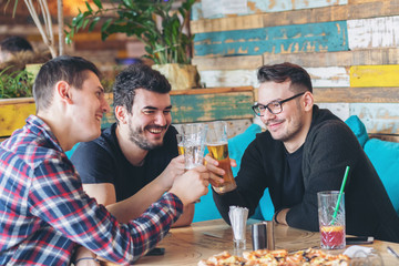 Happy men friends group drinking beer at brewery bar restaurant - Friendship concept with young men friends enjoying time and having genuine fun at cool vintage pub - Focus on center man