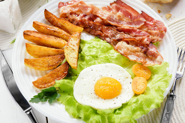Morning breakfast with delicious fried bacon. French fries and tender egg, close-up.