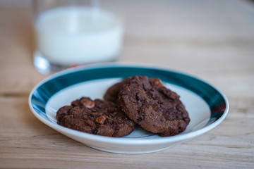 Close up of a plate of cookies with a glass of milk on the background