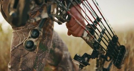 3bf700041cf4b3 0 13 Close up shot of bowhunter s hand carrying a compound bow and arrows  while he walks