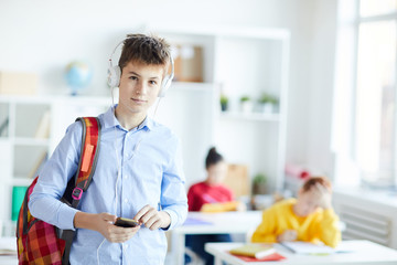 Contemporary schoolboy with backpack, smartphone and headphones standing in front of camera