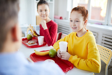 Two schoolgirls talking to classmate at lunch break while having drinks and fruit snack