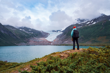Girl tourist looks at a glacier. Svartisen Glacier in Norway.