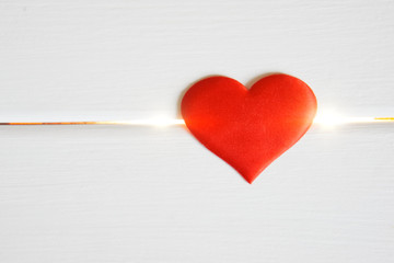 Red heart on a white wooden background and glowing lines. Health problems and cardiology