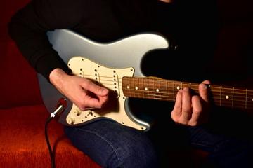 Man playing a electric guitar. Closeup, no face.