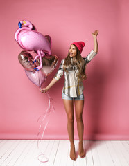 A beautiful young joyful girl is jumping holding a bunch of pink balloons on a pink pastel background.