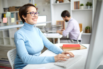 Cheerful employee in casual pullover sitting in fornt of computer, typing and laughing at something funny