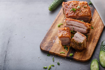 Chinese roasted pork belly on wooden cutting board copy space