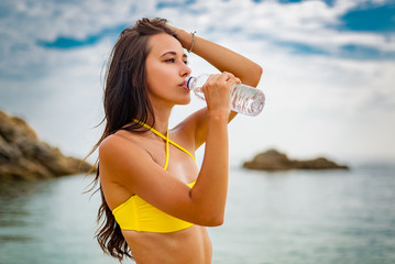 woman on the Beach drinking a cold water in bottle.