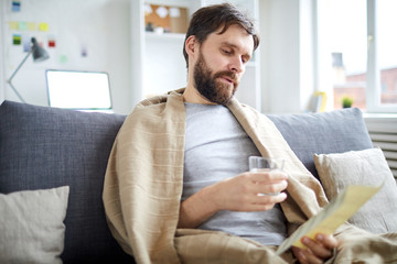 Bearded man with glass of water reading payment bill while sitting on sofa in living-room