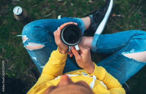 Top view girl holding in hands cup of hot tea on green grass