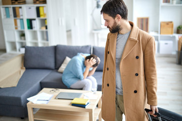 Young man in beige coat pulling suitcase while leaving for business travel on background of lonely woman
