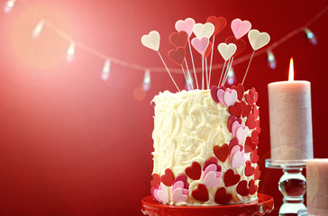 Beautiful St Valentine's Day party table with showstopper red, white and pink hearts double layer cake, with white chocolate frosting, with lens flare.