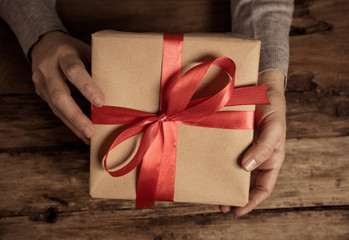 Close up o woman holding beautiful gift box wrapped with red ribbon for Valentines and anniversary