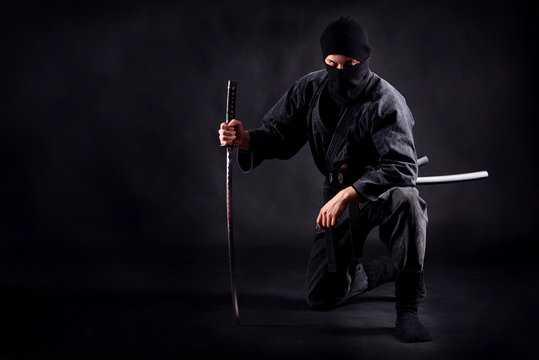 Ninja samurai crouched on one leg  and propped on a sword