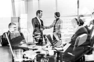 Sealing a deal. Business people shaking hands, finishing up meeting in corporate office. Business and entrepreneurship concept. Black and white image.