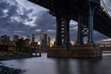 Brooklyn, NY / USA - OCT 19 2018: Lower Manhattan skyline and Manhattan bridge at sunset