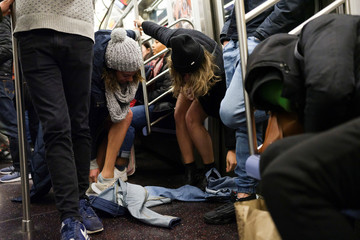 "Women participating in the annual ""No Pants Subway Ride""  remove their jeans in the Manhattan borough of New York City"