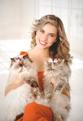 Portrait of elegant young woman holding two adorable Persian cats