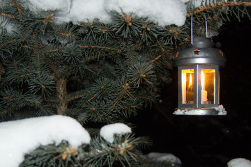 Lantern with burning candle on the snow in the evening.