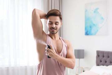 Handsome young man applying deodorant in bedroom