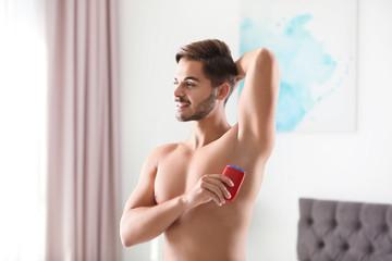 Handsome young man applying deodorant in room