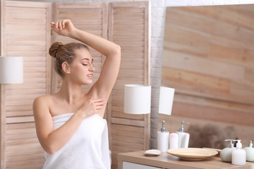 Beautiful young woman after shower in bathroom. Concept of using deodorant