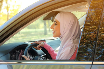 Modern Muslim woman in hijab driving car