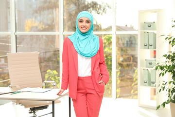 Modern Muslim businesswoman wearing hijab near table in light office