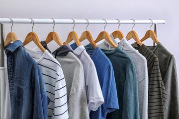 Stylish clothes hanging on wardrobe rack against light background