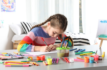 Little girl drawing picture at table with painting tools indoors