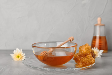 Glass bowl with tasty honey and dipper on gray table