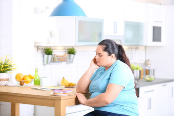 Sad overweight woman with donuts in kitchen. Failed diet