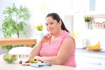 Overweight woman preparing salad in kitchen. Healthy diet