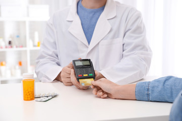Client using credit card for terminal payment in pharmacy, closeup