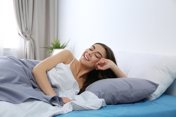 Young woman awakening at home in morning. Bedtime