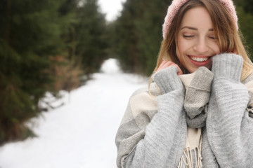 Young woman in snowy conifer forest, space for text. Winter vacation